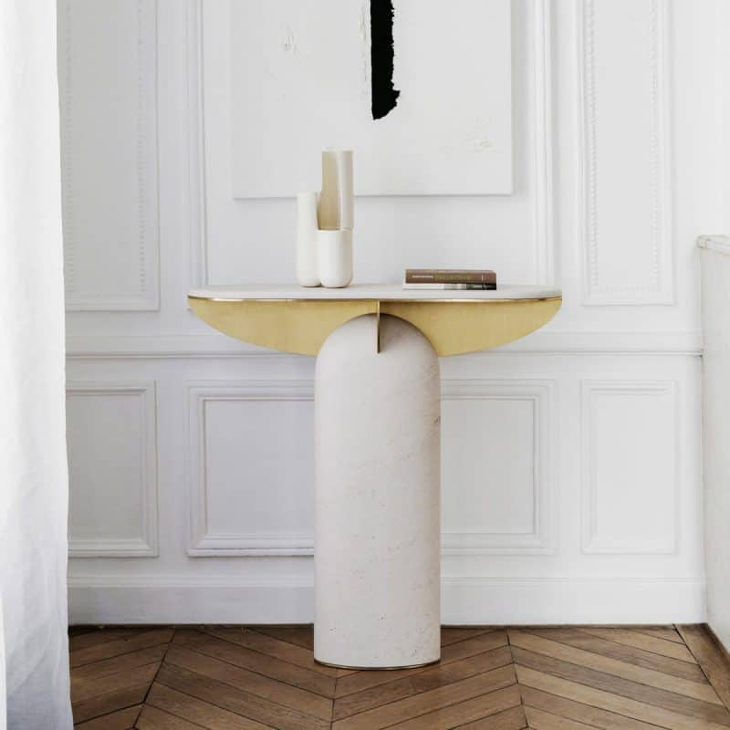 Console 03 made from travertine and brushed brass by designer Frédéric Saulou in a room with dark timber flooring
