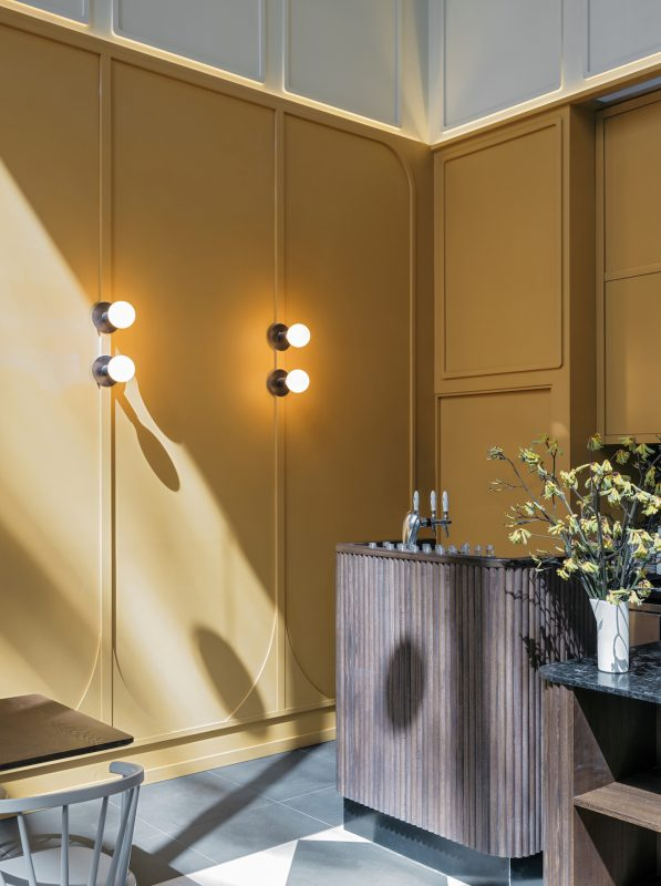 Detail of a corner in the Workshop Brothers Riverside Quay cafe featuring yellow wooden wall panelling, wall sconces with opaque glass spheres and a bar counter cladded with scalloped wood dowels.