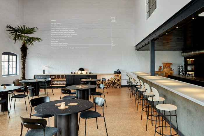 Restaurant interior with black dining chairs and cream bar stools in an industrial space