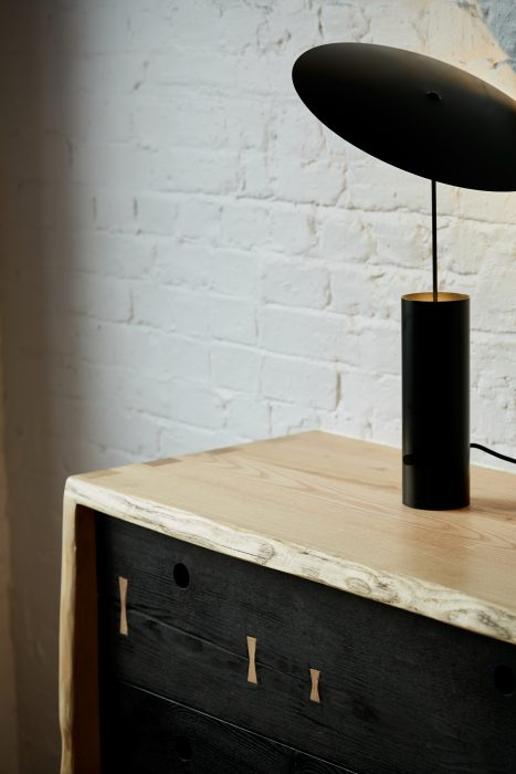 Asymmetric black table light by Innermost on a wooden sideboard