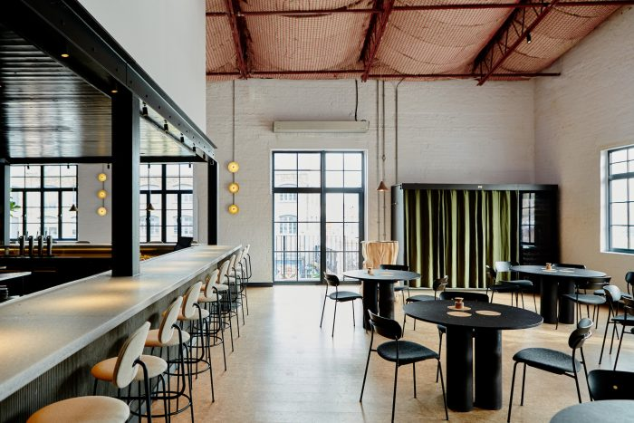 Restaurant interior in an industrial space featuring round tables, black dining chairs and a long bar counter.