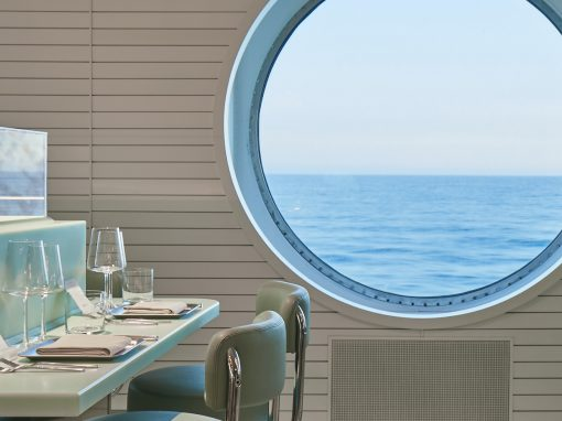 View onto the ocean through a large bull's eye window from a restaurant on the Scarlet Lady