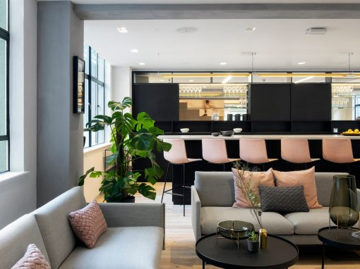 Open seating area in an office with grey sofas and pink barstools in front of a kitchen counter