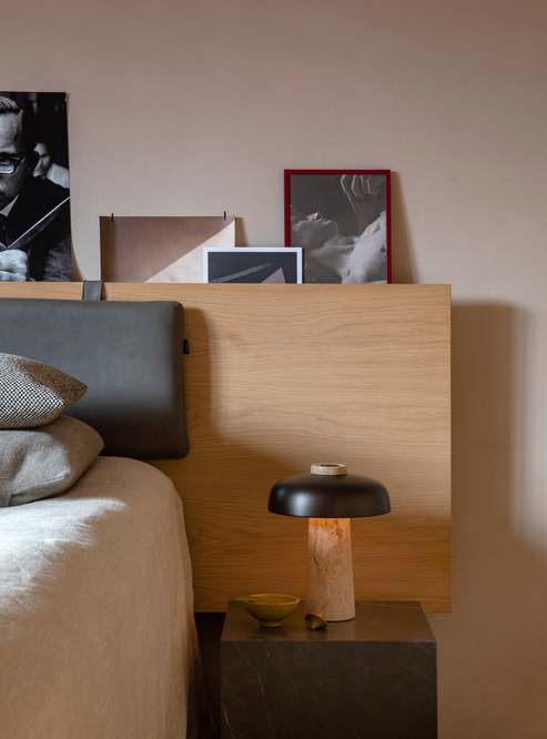 Reverset travertine table lamp by menu on a bedside table next to a bed with a wooden headboard