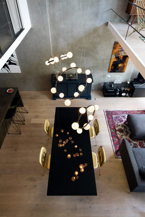 Open living and dining area with high ceilings and concrete walls featuring the Hubble Bubble pendants by Moooi