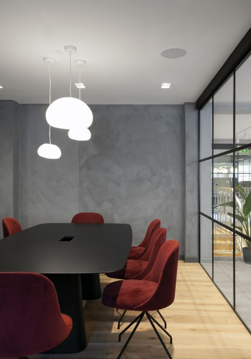 Meeting room with black table and red velvet chairs