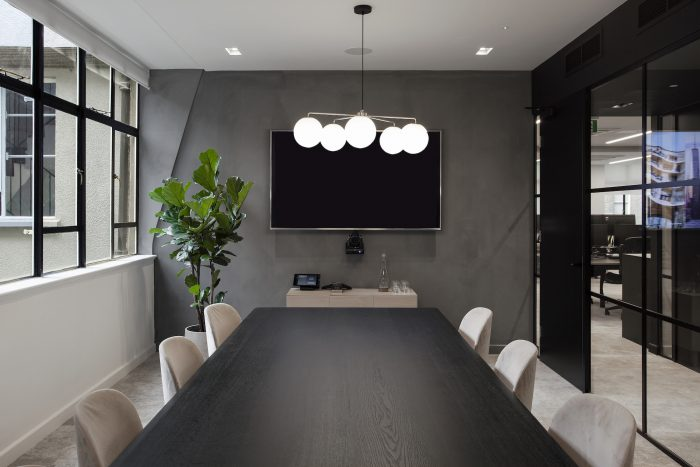 Meeting room with black table, grey fabric chairs and modern chandelier