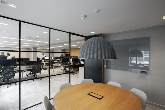 Meeting room with roudn wood table, grey fabric pendant and floor to ceiling windows.