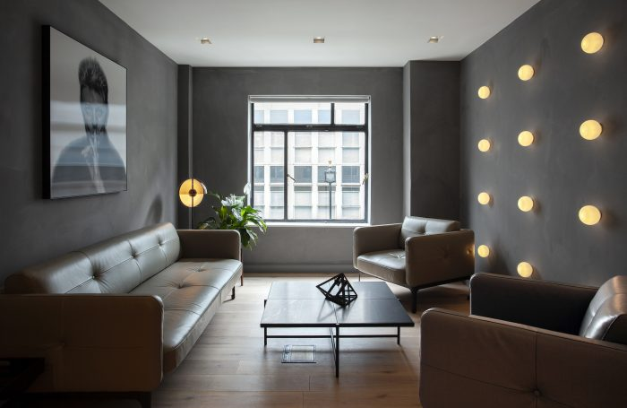 Office seating area with leather sofas and wall light installation